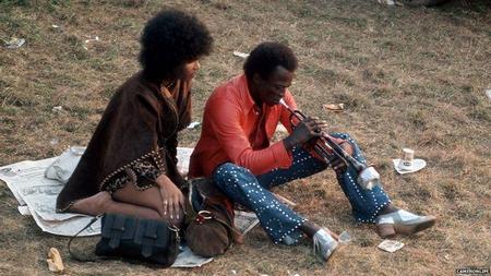 Miles Davis mentre prova sulla sabbia dell'isola di Wight in attesa di esibirsi nell'edizione 1970 del festival. In sua compagnia Betty Mabry che a detta del trombettista lo influenzò moltissimo riguardo alla sua svolta rock, che non riguardò solo la musica ma proprio il suo stile di vita.